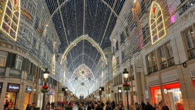 Einkaufsstraße mit vielen Menschen und Weihnachtsbeleuchtung.